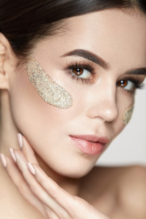 Photo pour Woman Face Skin Care. Portrait Of Beautiful Healthy Girl Touching Face With Beauty Product, Cosmetic Peeling Mask On Fresh Soft Skin. Closeup Of Sexy Female With Scrub On Facial Skin. High Resolution - image libre de droit