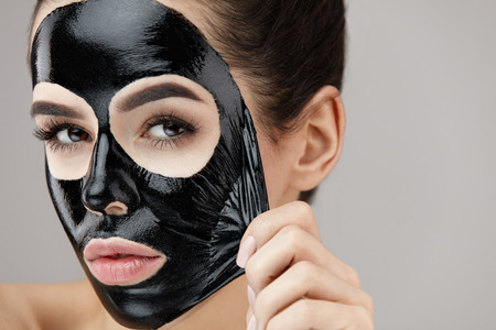 Photo pour Woman Face Care. Portrait Of Beautiful Girl Removing Cosmetic Black Peeling Mask From Facial Skin. Closeup Of Attractive Young Woman With Natural Makeup And Cosmetic Peel Mask On Face. High Resolution - image libre de droit