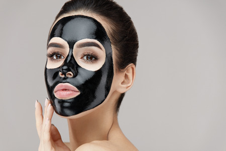 Foto de Female Beauty Face Skin Treatment. Closeup Beautiful Sexy Young Woman With Natural Makeup And Cosmetic Black Peel Mask On Facial Skin. Attractive Girl Applying Peeling Product On Face. High Resolution - Imagen libre de derechos