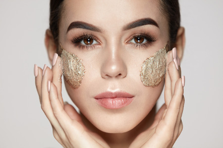 Photo pour Woman Face Skin Care. Closeup Beautiful Young Female Model With Natural Makeup Applying Scrub On Face. Portrait Of Attractive Girl Touching Soft Facial Skin With Cosmetic Product On. High Resolution - image libre de droit