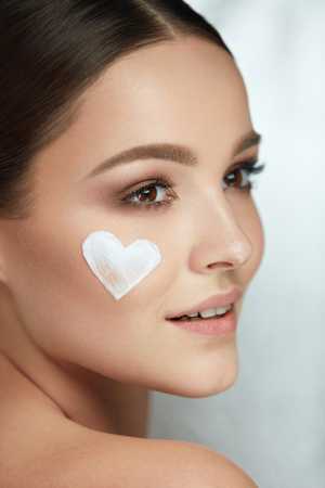 Photo for Beautiful Happy Woman With Heart Of Cream On Beauty Face Skin. Closeup Of Attractive Sexy Smiling Girl With Fresh Makeup And Heart-Shape Of Facial Cosmetic Product On Soft Smooth Skin. High Resolution - Royalty Free Image