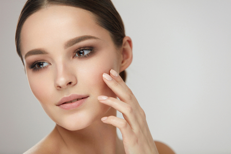 Foto de Woman Beauty Face Care. Closeup Of Attractive Young Female Touching Fresh Smooth Soft Facial Skin. Portrait Of Beautiful Sexy Girl Model With Natural Makeup Touching Face With Hand. High Resolution - Imagen libre de derechos