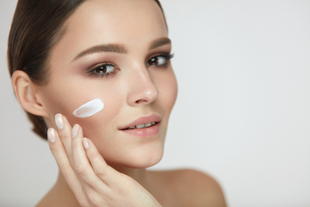 Photo for Beautiful Woman Face With Skin Care Cream On. Portrait Of Healthy Happy Female Applying Cream On Cheek. Closeup Beautiful Smiling Girl Putting Beauty Cosmetics On Fresh Soft Skin. High Resolution - Royalty Free Image
