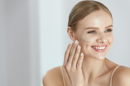 Photo pour Face Skin Scrub. Portrait Of Beautiful Smiling Female Applying Cosmetic Mask, Face Scrub On Facial Skin. High Resolution - image libre de droit