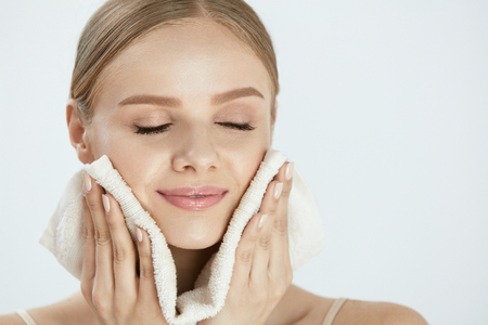 Photo pour Woman Cleaning Face With White Towel. Closeup Portrait Of Beautiful Happy Smiling Young Female Wiping Facial Skin With Soft Facial Towel After Washing Face. High Resolution - image libre de droit