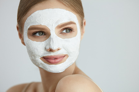 Photo for Skin Care Mask. Closeup Portrait Of Attractive Smiling Young Woman With White Clay Facial Mask On Healthy Fresh Face Skin. High Resolution - Royalty Free Image