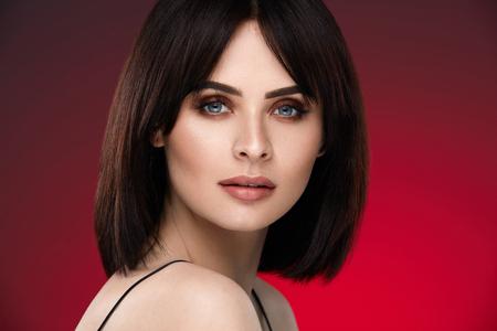 Foto de Beauty Woman Face. Closeup Of Beautiful Female Model With Soft Smooth Skin And Professional Facial Makeup. High Resolution - Imagen libre de derechos
