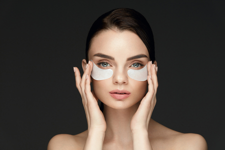Photo for Under Eye Treatment. Woman Face With Patches Under Eyes. Beautiful Young Female With Fresh Soft Skin Applying Beauty Patches Under Eyes On Black Background. High Resolution - Royalty Free Image