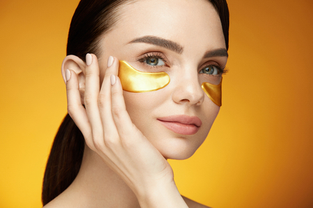 Photo pour Eye Skin Care Patches. Closeup Of Beautiful Smiling Girl Applying Gold Patches, Collagen Under Eye Mask On Face. Beauty Cosmetics. High Resolution - image libre de droit