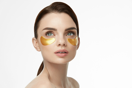 Foto de Woman Beauty Face With Mask Under Eyes. Beautiful Female With Natural Makeup And Gold Collagen Patches On Fresh Facial Skin. High Resolution - Imagen libre de derechos