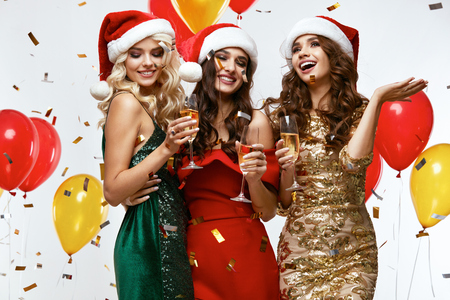 Foto de New Year's Party Time. Happy Girls Having Fun At Party. Sexy Smiling Young Women Dressed In Santa Hats And Fashionable Bright Dresses Holding Champagne Glasses At Celebration. High Quality Image. - Imagen libre de derechos