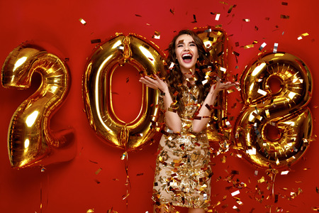 Photo for New Year. Woman With Balloons Celebrating At Party. Portrait Of Beautiful Smiling Girl In Shiny Golden Dress Throwing Confetti, Having Fun With Gold 2018 Balloons On Background. High Resolution. - Royalty Free Image