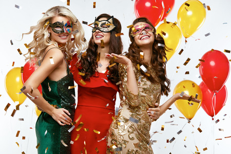 Foto de Holiday. Beautiful Women In Masks Celebrating New Year. Portrait Of Happy Girls In Festive Carnival Masks And Stylish Colorful Dresses Having Fun At Party. High Resolution. - Imagen libre de derechos