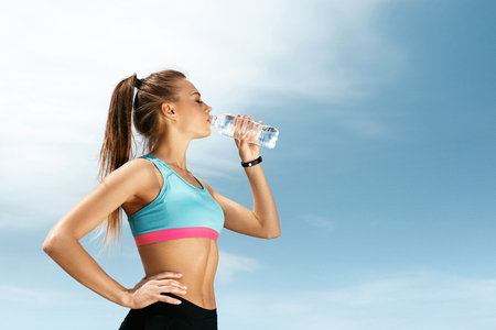 Photo for Woman Drinking Water After Running. Portrait Of Beautiful Athletic Girl In Bright Colorful Sportswear Resting After Fitness Workout, Drink Water From Bottle On Blue Sky Background. High Quality Image - Royalty Free Image