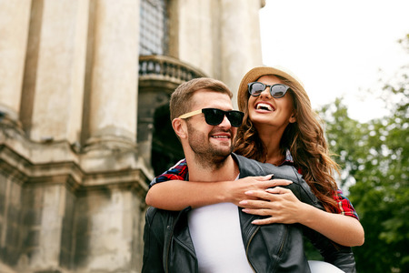 Photo for Tourist Couple. Beautiful Woman And Man Having Fun, Girl Hugging Man Behind His Back On Architecture Background. Portrait Of Smiling People Spending Time Together Outdoors. High Resolution - Royalty Free Image