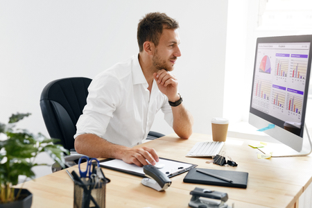 Foto de Young Business Man Working On Computer In Office. Portrait Of Handsome Businessman In White Shirt Sitting At Work Desk Looking At Monitor. High Quality Image. - Imagen libre de derechos