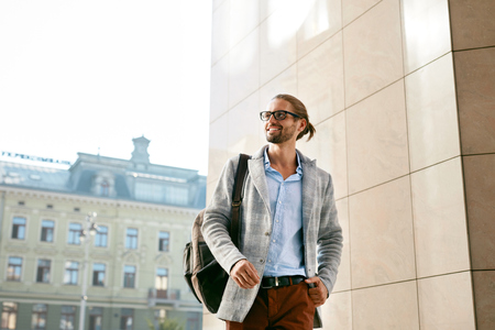 Photo pour Men Style. Handsome Smiling Man On Street. Fashionable Male Wearing Glasses And Business Casual Men's Attire With Backpack Walking On Sunny City Street. Office And Work Fashion Clothes. High Quality - image libre de droit