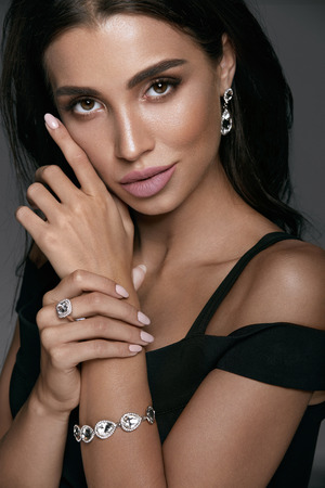 Foto de Jewelry Fashion. Beautiful Woman Wearing Diamonds. Portrait Of Gorgeous Female With Glamour Makeup On Beauty Face Wearing Black Evening Dress And White Gold Jewellery: Earrings, Bracelet And Ring - Imagen libre de derechos