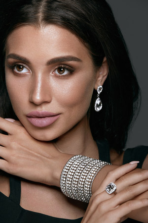 Photo pour Jewelry Fashion. Beautiful Woman Wearing Diamonds. Portrait Of Gorgeous Female With Glamour Makeup On Beauty Face Wearing Black Evening Dress And White Gold Jewellery: Earrings, Bracelet And Ring - image libre de droit