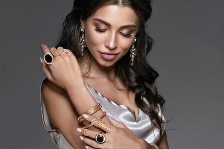 Photo pour Fashion And Beauty. Woman With Makeup In Jewelry. Portrait Of Sexy Young Female With Stylish Hairstyle Wearing Beautiful Accessories Such As Diamond Earrings, Gold Bracelets And Rings. High Quality - image libre de droit