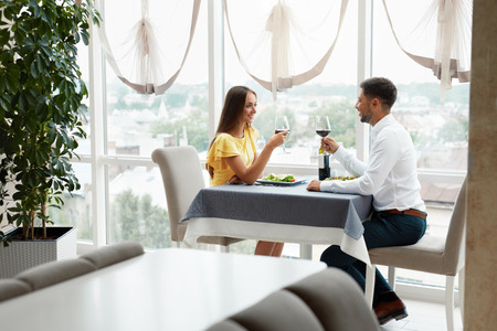 Photo pour Lovely Couple Having Dinner In Luxury Restaurant. Young Handsome Man And Beautiful Woman Drinking Red Wine Eating Salad. Romantic Relationship. High Quality Image. - image libre de droit