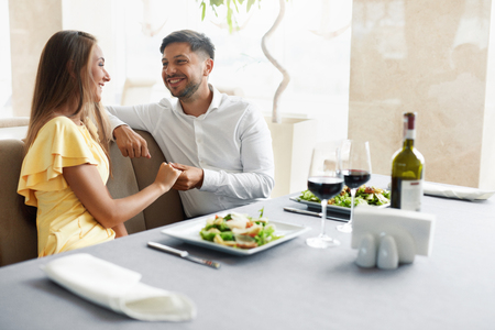 Foto de Romantic Couple Having Dinner For Two In Restaurant. Beautiful Happy People In Love Talking, Laughing, Flirting While Having Romantic Date With Wine And Food In Luxury Restaurant. High Quality Image. - Imagen libre de derechos