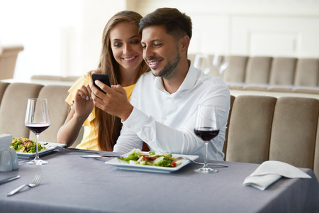 Photo pour Couple In Love Looking On Phone Having Dinner In Restaurant. Lovely Young People Using Phone And Having Romantic Dinner In Restaurant. Relationships Concept. High Resolution. - image libre de droit