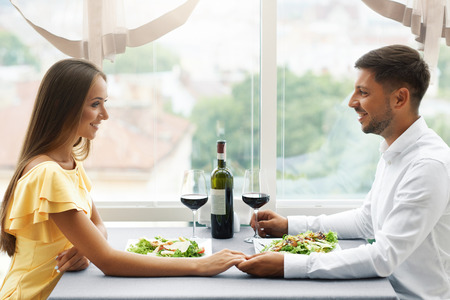 Photo pour Romantic Couple Having Dinner For Two In Restaurant. Beautiful Happy People In Love Talking, Laughing, Flirting While Having Romantic Date With Wine And Food In Luxury Restaurant. High Quality Image. - image libre de droit