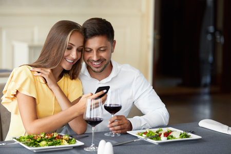 Foto de Couple In Love Looking On Phone Having Dinner In Restaurant. Lovely Young People Using Phone And Having Romantic Dinner In Restaurant. Relationships Concept. High Resolution. - Imagen libre de derechos