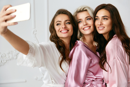 Foto de Beautiful Women Making Photos On Phone At Home Party. Beautiful Smiling Female Friends With Sexy Hairstyle And Makeup In Silk Pink Robes Taking Selfies And Having Fun At Pajama Party. High Quality - Imagen libre de derechos
