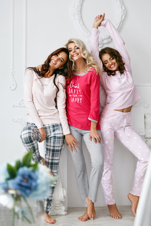 Photo pour Girls In Pajamas. Beautiful Friends In Home Clothes. Gorgeous Smiling Young Female Models Having Fun And Enjoying Pajamas Party In Light Home Interior. Women Nightwear Clothing. High Quality Image - image libre de droit