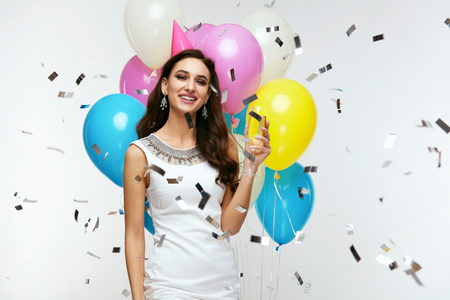 Photo for Smiling Girl Drinking Champagne With Balloons And Flying Confetti On Background. Holiday Celebration. High Quality Image. - Royalty Free Image