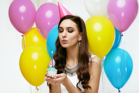 Photo pour Portrait Of Beautiful Smiling Woman In Festive Dress And Birthday Hat Holding Cupcake With Candle In Hands, Celebrating Holiday. High Resolution. - image libre de droit