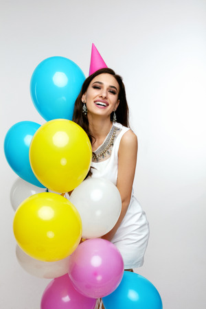Photo pour Portrait Of Smiling Young Female In Stylish White Dress With Balloons Having Fun And Celebrating Her Birthday Party. Holiday. High Quality - image libre de droit