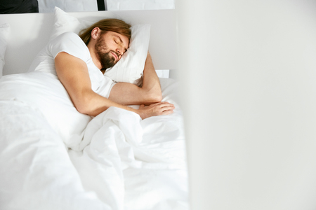 Photo pour Man Sleeping On Bed In Morning. Portrait Of Handsome Young Male With Beard Resting On White Linen In Light Bedroom. Healthy Sleep. High Quality Image. - image libre de droit