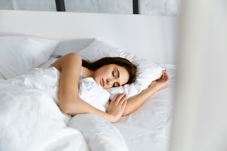 Photo pour Sleep. Young Woman Sleeping In Bed. Portrait Of Beautiful Female Resting On Comfortable Bed With Pillows In White Bedding In Light Bedroom In Morning. People Sleep. High Quality Image. - image libre de droit