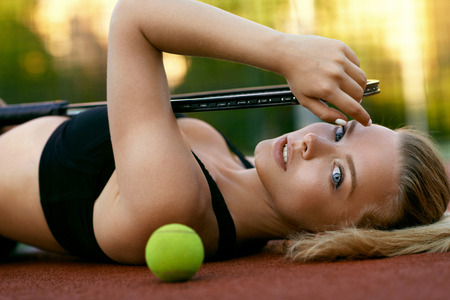 Photo for Sports. Beautiful Woman After Playing Tennis On Court. Portrait Of Female With Natural Face Makeup Holding Tennis Racket Lying On Ground And Resting After Training Outdoors. High Quality Image. - Royalty Free Image