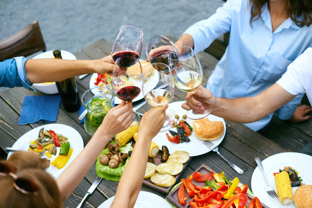 Photo pour People Cheering With Drinks At Outdoor Dinner Party. Close Up Of Friends Hands Raising Toast With Glasses Of Wine, Enjoying Outdoor Picnic While Sitting At Table With Food. Cheers. High Quality Image. - image libre de droit