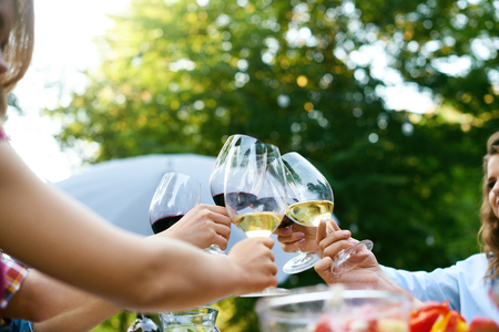 Foto de People Cheering With Drinks At Outdoor Dinner Party. Close Up Of People Hands Raising Toast With Glasses Of Wine, Enjoying Outdoor Picnic In Nature. High Quality Image. - Imagen libre de derechos