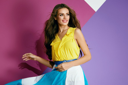 Foto de Fashion Clothes. Beautiful Woman In Colorful Dress In Summer. Fashionable Smiling Girl In Stylish Yellow Blouse And Trendy Colorful Skirt On Violet Background. Female Summer Style. High Quality - Imagen libre de derechos