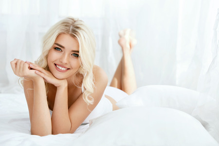 Photo pour Beautiful Happy Woman On Bed In Light Interior. Attractive Happy Young Female With Blonde Hair, Healthy Smooth Soft Skin And Natural Facial Makeup Lying On White Bedding. Skin Care. High Quality - image libre de droit