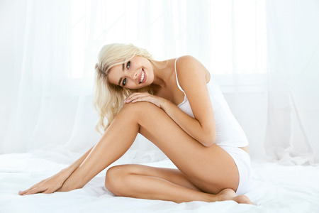 Photo for Smiling Woman With Fit Body And Beautiful Legs On White Bed. Happy Girl In White Underwear With Soft Depilated Body Skin, Natural Hair And Beauty Face In Light Interior. Women Skin Care. High Quality - Royalty Free Image