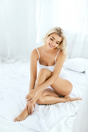 Foto de Smiling Woman With Fit Body And Beautiful Legs On White Bed. Happy Girl In White Underwear With Soft Depilated Body Skin, Natural Hair And Beauty Face In Light Interior. Women Skin Care. High Quality - Imagen libre de derechos