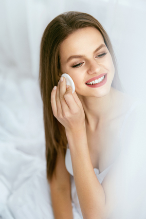 Photo pour Removing Makeup. Beautiful Female Cleaning Face White Cosmetic Cotton Pad. Young Blonde Woman Taking Off Makeup From Fresh Facial Skin With Cosmetic Pad. Face Skin Care Concept. High Quality Image. - image libre de droit