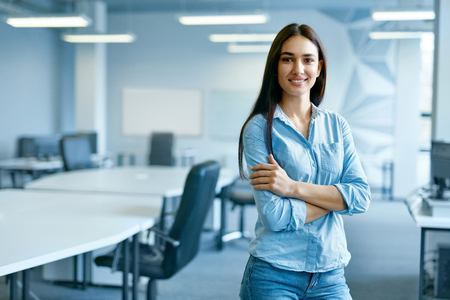 Photo for Woman In Office. Female At Work In Light Modern IT Office. Portrait Of Beautiful Smiling Young Worker In Casual Clothes With Arms Crossed At Workplace. Business Person, People At Work. High Quality - Royalty Free Image