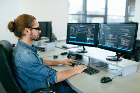 Photo pour Programming. Man Working On Computer In IT Office, Sitting At Desk Writing Codes. Programmer Typing Data Code, Working On Project In Software Development Company. High Quality Image. - image libre de droit