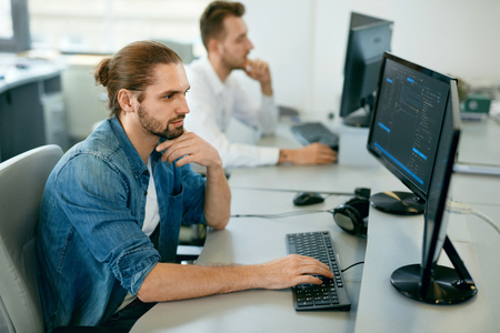 Foto de Programmers Working, Looking At Computer In IT Office. Handsome Young Men In Casual Closes Typing Codes, Working On Computer While Sitting At Workplace. High Quality Image. - Imagen libre de derechos