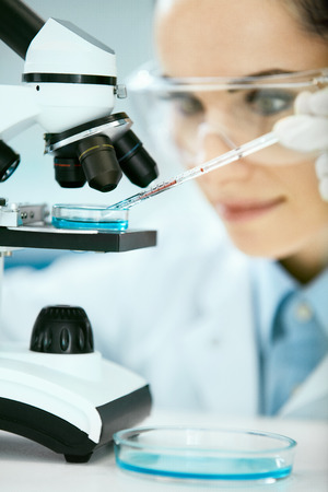 Foto de Medical Analysis. Female Scientist Doing Test In Laboratory. Close Up Of Young Woman Doctor In Medicine Glasses Using Microscope, Researching, Working In Light Modern Laboratory Clinic. High Quality - Imagen libre de derechos