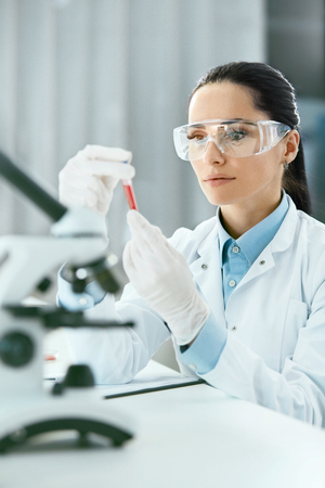 Foto de Laboratory. Woman Doing Medical Research With Blood. Portrait Of Beautiful Young Female In White Coat Sitting At Workplace And Working With Blood Sample In Lab. Medical Laboratory. High Resolution - Imagen libre de derechos
