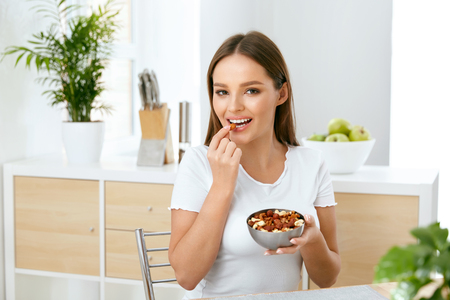 Photo for Healthy Nutrition. Beautiful Young Woman Eating Nuts - Royalty Free Image
